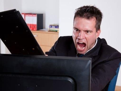 homme énervé frappe son écran avec un clavier